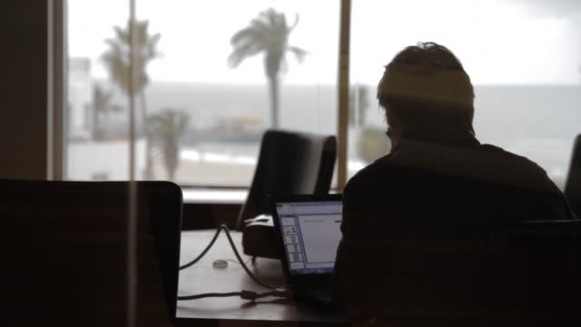 man sits alone in a dark office space
