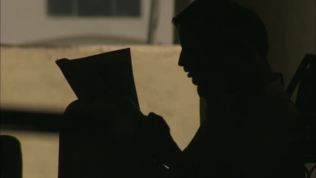 A man sits and reads a newspaper in silhouette.