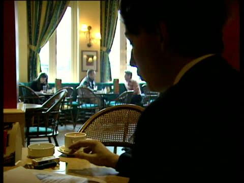 vídeos de stock e filmes b-roll de man sits at table in public house smoking cigarette england - smoke physical structure