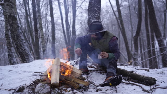 man sits by campfire in forest drinking coffee to stay warm - one man only stock videos & royalty-free footage