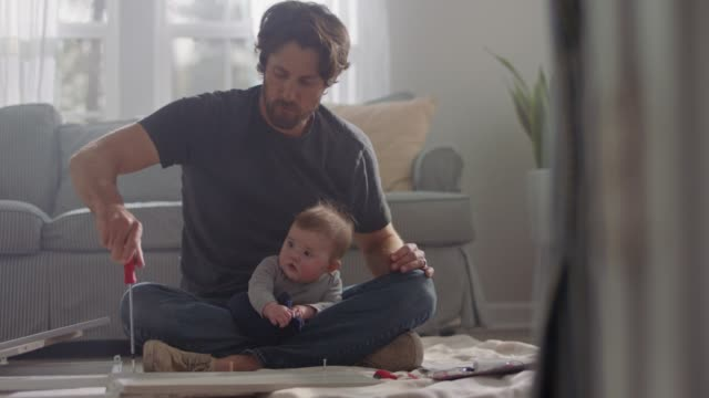 man sits cross legged with baby in lap as he assembles flat pack furniture with screwdriver. - bricolage video stock e b–roll