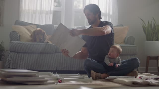 vídeos de stock, filmes e b-roll de man sits cross legged with baby in lap as he looks at directions to assemble flat pack furniture. - prateleira mobília