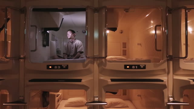 ms a man sits cross-legged in a capsule hotel watching television / tokyo, japan - cross legged stock videos & royalty-free footage