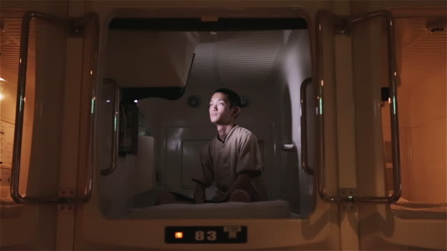MS A man sits cross-legged in a capsule hotel watching television / Tokyo, Japan