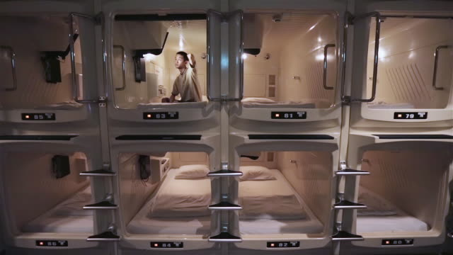 ws a man sits in a capsule hotel watching television / tokyo, japan - hotel stock-videos und b-roll-filmmaterial