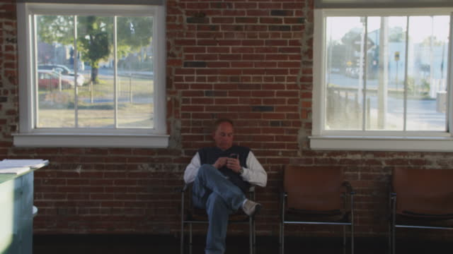 Man sits in a chair in a waiting room using his mobile smart phone, shot against a brick wall