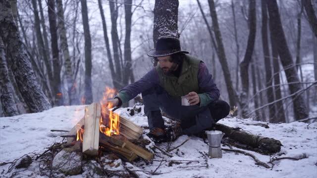 vidéos et rushes de man sits in forest making campfire drinking coffee - un seul homme d'âge moyen