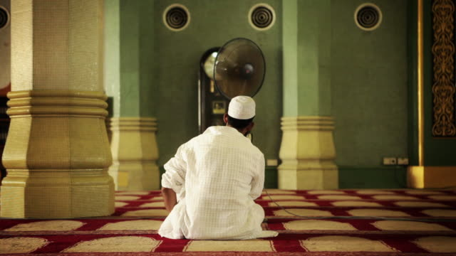 A man sits in front of a fan at a mosque.