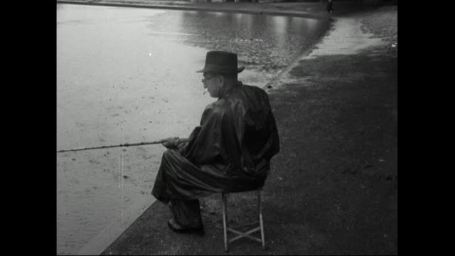 man sits in rain by a pond fishing in london park;1951 - 1951 stock videos & royalty-free footage