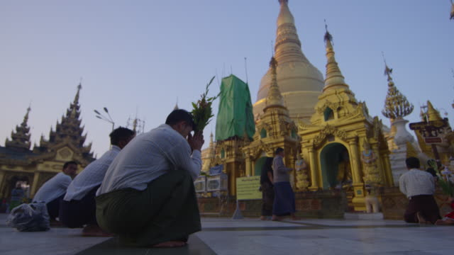 Man sits low and prays at temple in Myanmar