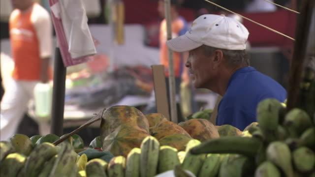 vídeos de stock, filmes e b-roll de a man sits next to piles of plantains at a street market. - banana de são tomé