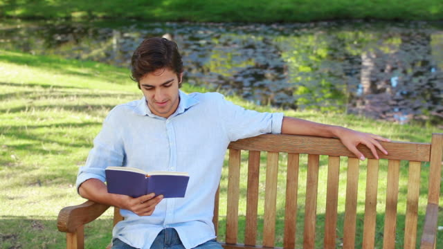 man sits on a bench while reading a book - nur junge männer stock-videos und b-roll-filmmaterial