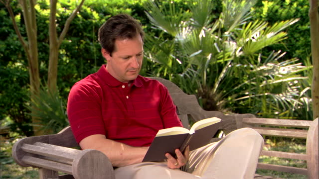 A man sits on a bench reading a book.