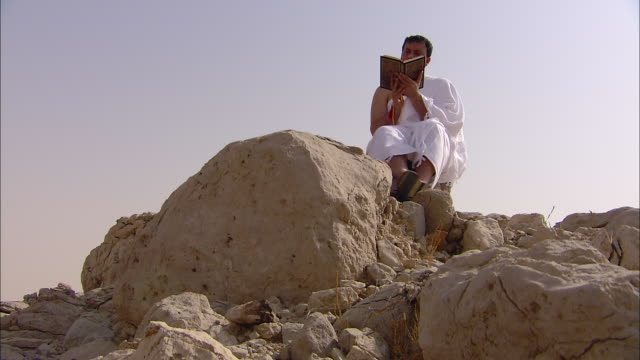 A man sits on a boulder as he reads a book.
