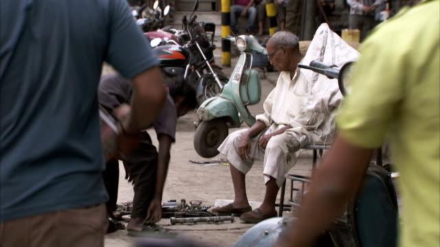 a man sits on a delhi street. - delhi stock videos & royalty-free footage