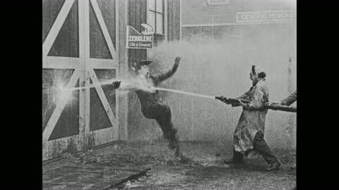 1920 man (fatty arbuckle) sits on a hole in a fire hose to keep the water from spraying out, but he gives up when a trolley runs over the hose and creates new holes - slapstick comedy stock videos & royalty-free footage