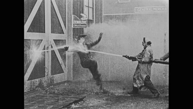 vídeos y material grabado en eventos de stock de 1920 man (fatty arbuckle) sits on a hole in a fire hose to keep the water from spraying out, but he gives up when a trolley runs over the hose and creates new holes - fire hose
