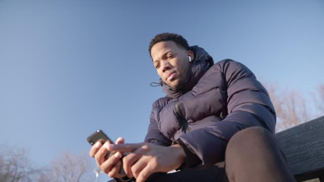 mann sitzt auf derbank und hört musik, schaut auf die aussicht - sitting stock-videos und b-roll-filmmaterial