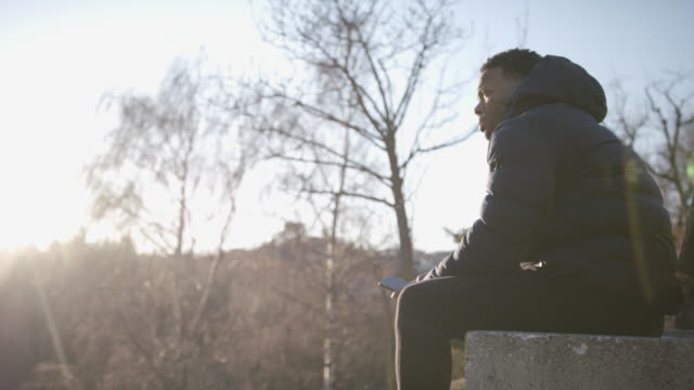 man sits on bench listening to music, looks out at view - bench stock videos & royalty-free footage