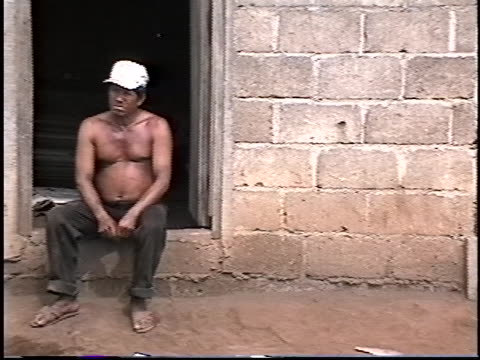 man sits on his door stoop, while boys play nearby, in the village of posoltega, nicaragua. nicaragua is one of the poorest countries in the western... - マナグア点の映像素材/bロール