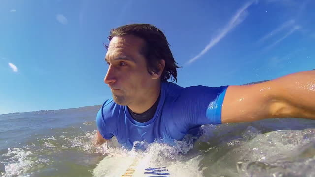 pov: man sits on surfboard waiting for a wave - oar stock videos & royalty-free footage