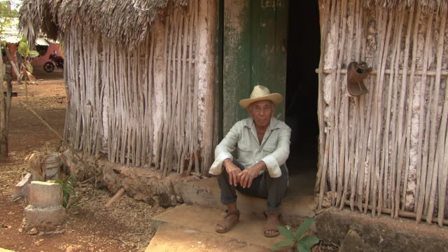 a man sits on the step of a mayan hut, mexico - shack stock videos & royalty-free footage
