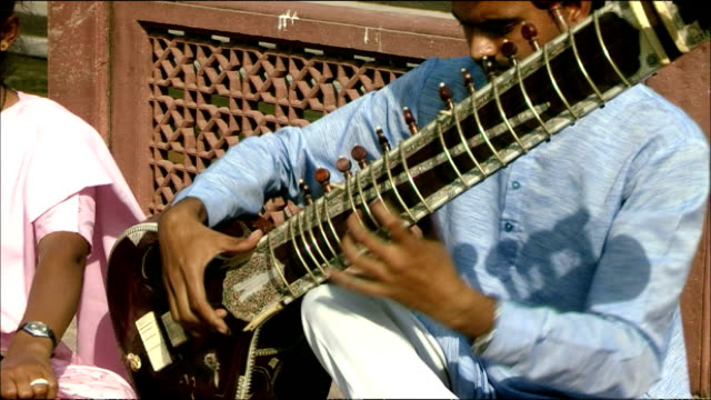 Man sits playing sitar at Agra Fort, Agra