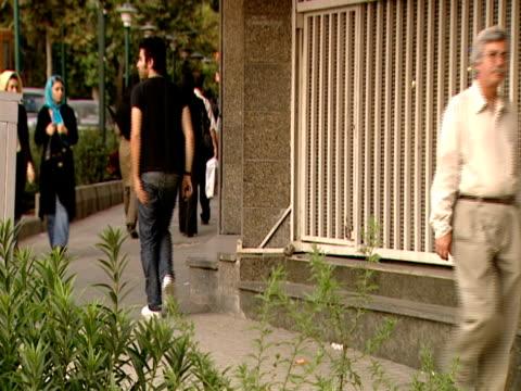 vidéos et rushes de man sitting against building and shoppers walking down sidewalk glancing at purses in window / tehran, iran - format vignette