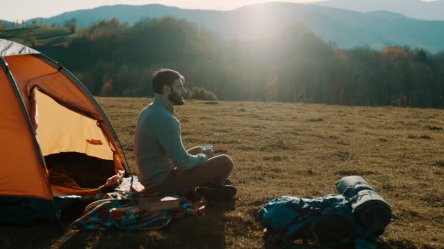 Man sitting and drinking coffee on camping trip on mountain