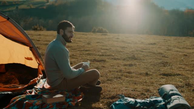 mann, sitzen und trinken kaffee auf camping-ausflug am berg - überleben stock-videos und b-roll-filmmaterial