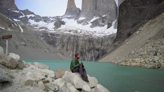 vídeos de stock e filmes b-roll de man sitting and photographing at fitz roy mountain in patagonia - argentina