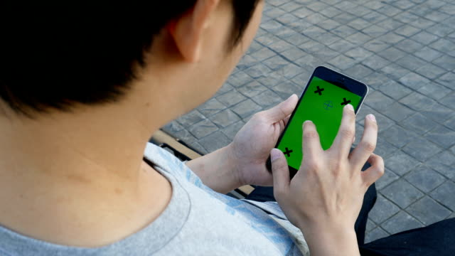 Man sitting and playing smartphone