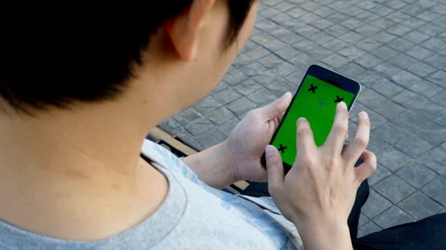 Mann sitzen und spielen smartphone