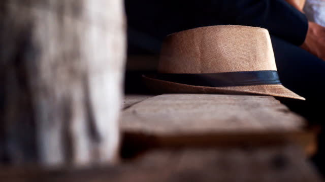 a man sitting and put his hat beside him. - straw hat stock videos and b-roll footage