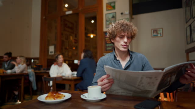 man sitting and reading newspapers in local cafe early in the morning - bar video stock e b–roll