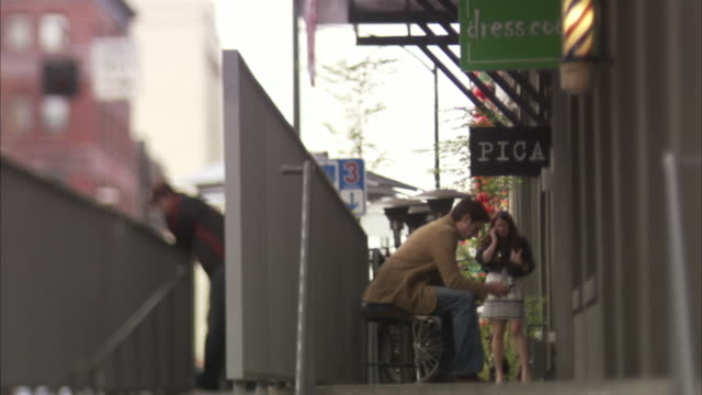 ws man sitting and text messaging in front of coffee shop, people in background / portland, oregon, usa - portland oregon点の映像素材/bロール