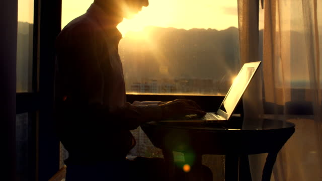 man sitting and typing on laptop by window - human body part stock videos & royalty-free footage