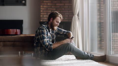man sitzt und mit telefon im wohnzimmer - männer stock-videos und b-roll-filmmaterial