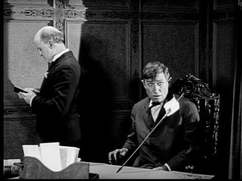 1924 B&W MS man sitting as arrow with note sticks into desk