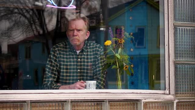 man sitting at bar in window of coffee shop - 見つめる点の映像素材/bロール