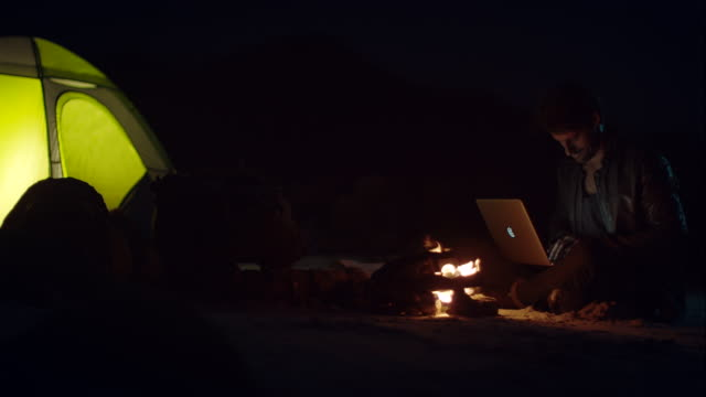 man sitting at campfire with his laptop - extreme terrain stock videos & royalty-free footage