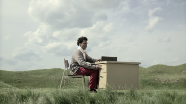 Man sitting at desk in a field, looking in draw then walking away with briefcase