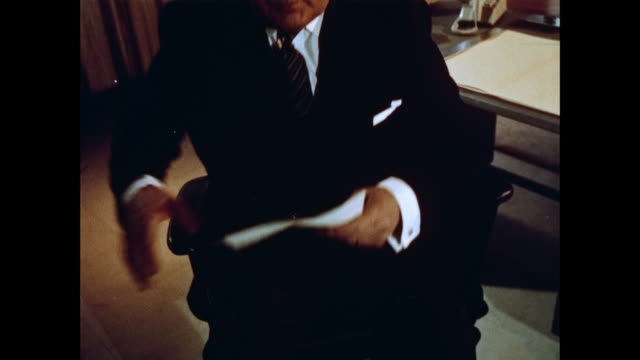MONTAGE Man sitting at desk in office answering telephone / United Kingdom