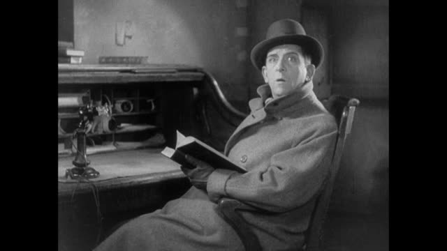 "1931 man sitting at desk reading book, looks up and says ""on gluten"" - reading stock videos & royalty-free footage"