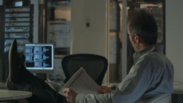 MS Man sitting at desk reading newspaper in server room, Sydney, Australia