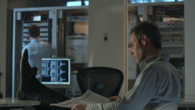 MS Man sitting at desk reading newspaper, other man working on server in background, Sydney, Australia