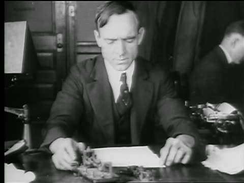 b/w 1927 man sitting at desk sending message on telegraph / newsreel - telegraph machine stock videos & royalty-free footage