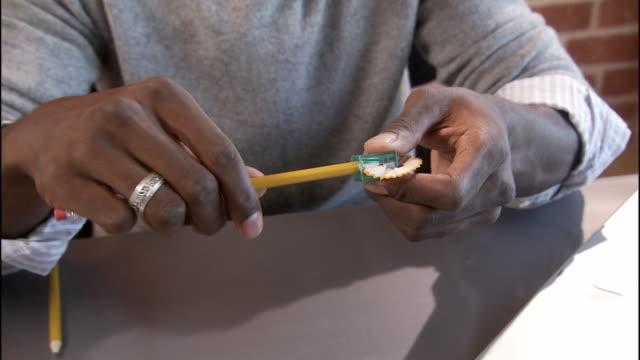 vídeos y material grabado en eventos de stock de cu, zo, zi, tu, td, man sitting at desk sharpening pencil, los angeles, california, usa - sacapuntas