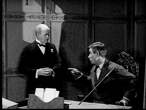 1924 b&w ms man sitting at desk with butler standing by/ man saying somehting shocking to butler before getting up and leaving  - 1924 stock-videos und b-roll-filmmaterial