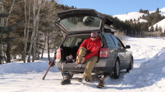 man sitting at the back of car putting on ski boots / ketchum, idaho, united states - attrezzatura sportiva video stock e b–roll